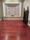 Cherry red hardwood floor, black fireplace, green walls